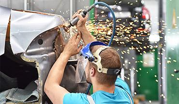 Mecánico trabajando la chapa de un coche